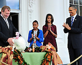 United States President Barack Obama, right, accompanied by his daughters Malia, left center, and Sasha, center, applauds after pardoning the National Thanksgiving Turkey, Liberty, in a  ceremony on the North Portico of the White House in Washington, D.C. on Wednesday, November 23, 2011.  Liberty, a 19-week old, 45-pound Turkey will live out its life at George Washington's Mount Vernon Estate and Gardens in Mount Vernon, Virginia. At left is National Turkey Federation Chairman Richard Huisinga..Credit: Ron Sachs / CNP.(RESTRICTION: NO New York or New Jersey Newspapers or newspapers within a 75 mile radius of New York City)