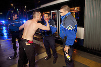 "Switzerland. Geneva. Jonction neighborhood. Three police officers listen to a bloody and bare-chested man from Kosovo. The young man hurts himself on the right hand in a fight during a bus ride in the late night. The policemen will let him go freely back home. The policeman (R) holds a pepper spray in his hand. Pepper spray, also known as OC spray (from ""Oleoresin Capsicum""), OC gas, and capsicum spray, is a lachrymatory agent (a chemical compound that irritates the eyes to cause tears, pain, and even temporary blindness) used in policing. Its inflammatory effects cause the eyes to close, taking away vision. This temporary blindness allows officers to more easily restrain subjects. 6.05.12 © 2012 Didier Ruef"
