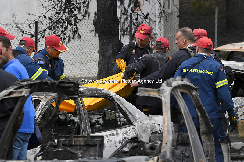 Pictured: Firemen recover a body from a burned car in the aftermath of the forest fire which has claimed dozens of lives in the Mati area of Rafina, Greece. Tuesday 24 July 2018<br /> Re: Deaths caused by wild forest fires throughout Greece.