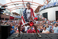 Kansas City, MO - Monday, June 16, 2014:  A USA soccer fan dances for a free can of beer during half-time at a public viewing in the Power and Light District of Kansas City, Missouri for the USA vs. Ghana first round World Cup match