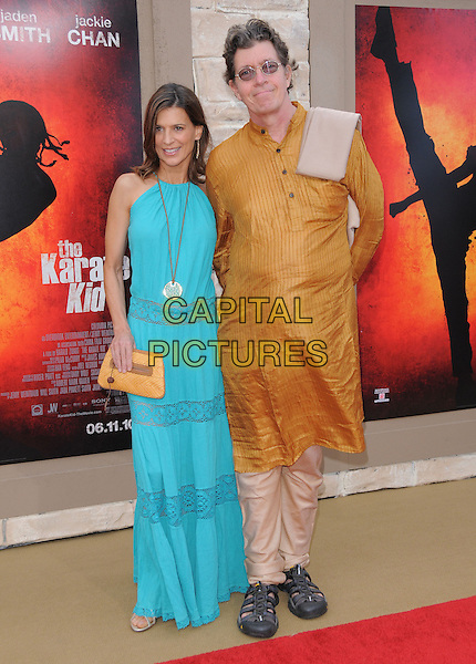 PERREY REEVES & GUEST.L.A. Premiere of The Karate Kid held at The Mann Village Theatre in Westwood, California, USA..June 7th, 2010 .full length long maxi turquoise dress hand on hip necklace lace sheer tan brown clutch bag.CAP/RKE/DVS.©DVS/RockinExposures/Capital Pictures.