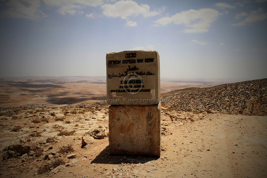 """A sign is seen on the way to Jenba a Palestinian town of 50 families seats in an area called by the IDF as """"Firing Zone 918"""" and is located in the southern Hebron hills near the town of Yatta.  Spread over 30,000 dunams, it includes twelve Palestinian villages.  According to OCHA figures, 1,622 people lived in the area in 2010, and according to local residents the number of inhabitants currently stands at about 1,800. For over a decade, the residents of twelve uniquely traditional Palestinian villages in the area of Masafer-Yatta in the south Hebron hills have lived under the constant threat of demolition, evacuation, and dispossession.<br /> <br /> The State's insistence on evacuation of Firing Zone 918 in part or in whole, if acceptance by the HCJ, might result in an immediate humanitarian disaster for almost two thousand souls, the destruction of villages, and the eradication of a remarkable way of life that has endured for centuries."""
