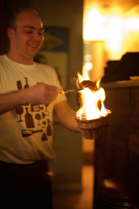 LISBON, PORTUGAL - November 21, 2015: A waiter serves flaming chori&ccedil;o at Artis Wine Bar in the Bairro Alto district.<br /> <br /> CREDIT: Clay Williams.<br /> <br /> &copy; Clay Williams / claywilliamsphoto.com