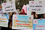 """Palestinian women hold placards and shout slogans during a rally to protest against the rising incidents of violence against women in Gaza City March 03, 2014. Twenty-six women were slain by relatives in the West Bank and Gaza in 2013, twice as many as the year before, according to official figures. The rise stems from mounting economic difficulties in the Palestinian territories, compounded by ongoing leniency for those killing in the name of """"family honor"""" and social acceptance of violence against women, women's rights activists said. Photo by Ashraf Amra"""