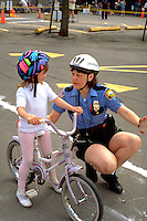 Officer with participant age 35 and 6 at community Youth Express Bicycle Safety Rodeo.  St Paul Minnesota USA