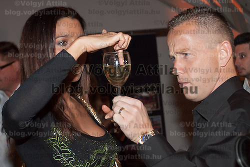 "Reka Rubint (L) and Norbert ""Norbi"" Schobert (R) concentrate on a glass of champagne during the birthday party of Hungarian celebrity Peter Hajdu (not in picture) celebrating the 35th birthday of the TV personality in Budapest, Hungary on April 08, 2010. ATTILA VOLGYI"
