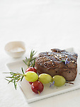 Beef steak served with skewered red and green grapes, rosemary