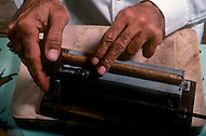 Cuba, March 1992: Controlling and fixing the length of the cigar after finishing the cigar, In La Corona, the largest Cigar factory in Havana.