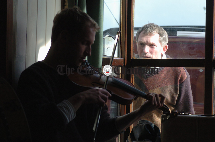 An interested party peeps through a pub window as Adam Shapirotakes part in a session during Fleadh na gCuach in Kinvarra.Photograph by John Kelly.