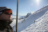 USA, California, Mammoth, a skier looks up at the snow covered mountain during his ride up the chairlift at Mammoth Ski Resort