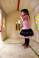 Milpitas, CA -- February 26, 2012: A happy three-year-old recipient stands  inside her new playhouse, one of two built by Stanford student-athletes at at Habitat for Humanity Silicon Valley's Milpitas workshop.  <br /> <br /> This house was for a Blue Star family with a three-year-old daughter and the other was built for Environmental Volunteers, an Educational organization located in Palo Alto, California.