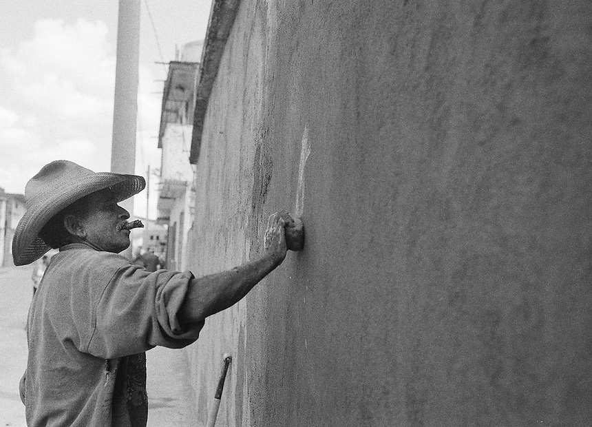 A man repairs a wall in Santa Clara, Cuba.