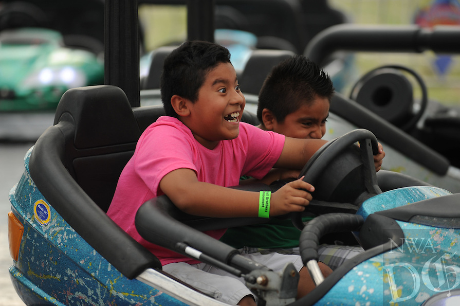 NWA Democrat-Gazette/ANDY SHUPE<br /> Children laugh Tuesday, Aug. 4, 2015, while riding the bumper cars during the 117th annual Tontitown Grape Festival. The festival continues through Saturday. Visit nwadg.com/photos to see more photographs from the festival.