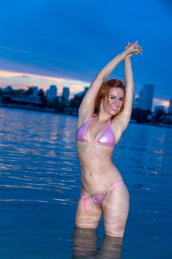 Young seductive female posing and standing in the water with arms up during sunset