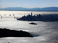 aerial photograph of the silhouette of the San Francisco skyline, Angel Island, in the foreground, Alcatraz Island in the middle of the photograph, Numerous vessed anchored at Anchorages 8 and 9 behind the San Francisco Bay Bridge.
