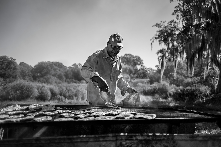 "Julius ""Frank"" Bailey smokes freshly caught mullet on a grill in his back yard in Hog Hammock. The Geechee have held on to their traditional self-sustaining practices of fishing, farming and hunting."
