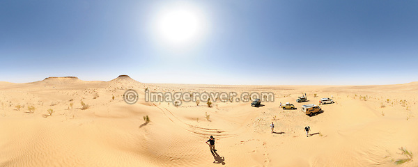 Africa, Tunisia, Tembaine. Desert travellers with their five historic Series Land Rover vehicles at the Tembaine peaks in southern Tunisia's Sahara desert. This is a stitched panorama image with a 360 degree horizontal field of view. --- Info: Image belongs to a series of photographs taken on a journey to southern Tunisia in North Africa in October 2010. The trip was undertaken by 10 people driving 5 historic Series Land Rover vehicles from the 1960's and 1970's. Most of the journey's time was spent in the Sahara desert, especially in the area around Douz, Tembaine, Ksar Ghilane on the eastern edge of the Grand Erg Oriental.