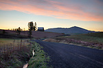 Idaho, North, Latah County, Palouse, Moscow, Potlatch. Morning twilight on a country road with barn in spring.