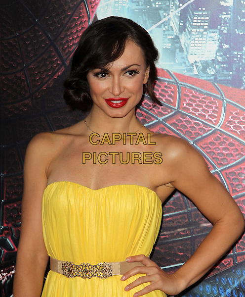 "Karina Smirnoff.Los Angeles Premiere Of ""The Amazing Spider-Man"" Held The at Regency Village Theatre, Westwood, California, USA..June 28th, 2012.half length dress beige belt yellow red lipstick strapless hand on hip.CAP/ADM/FS.©Faye Sadou/AdMedia/Capital Pictures."