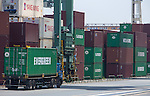 Tokyo, Japan - A truck drives past a pile of containers in cargo area at a port in Tokyo, May 22, 2013. Japan posts a record-high of 879.9 billion yen ($8.6 billion USD) trade deficit for April as the weaker yen caused the increase the costs of imports.
