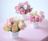 Three flower arrangements in small aluminium buckets