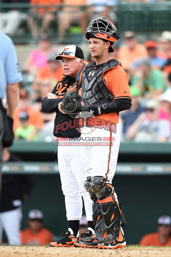 Baltimore Orioles manager Buck Showalter and catcher Caleb Joseph (63) wait on a call during a spring training game against the Pittsburgh Pirates on March 23, 2014 at Ed Smith Stadium in Sarasota, Florida.  Baltimore and Pittsburgh tied 7-7.  (Mike Janes/Four Seam Images)