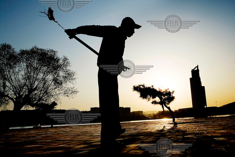 A man sweeps beside the local headquarters of PetroChina, seen in the distance with a curved solar panel on its roof..This may seem to be indicative of an environmentally responsible company, but the safety level at its chemical factories along the Songhua River is alarming....