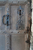 England. Old wooden door with big keyhole and metal handles.
