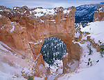 Bryce Canyon National Park, UT<br /> Natural Bridge covered with fresh snow with clearing storm clouds