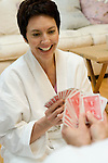 Mature woman playing cards with her mate, smiling