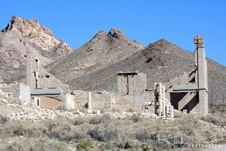 The remains of the Cook Bank Building, with the Rainbow Mountains in the background, in Rhyolite, Nevada. The building was built in the 1900's at a cost of $90,000 and included marble floors imported from Italy, mahogany woodwork, electrict lights, telephone, and inside plumbing. By 1910 parts off the building were being sold off and by 1919 the building was no longer in use. Photographed 03/08