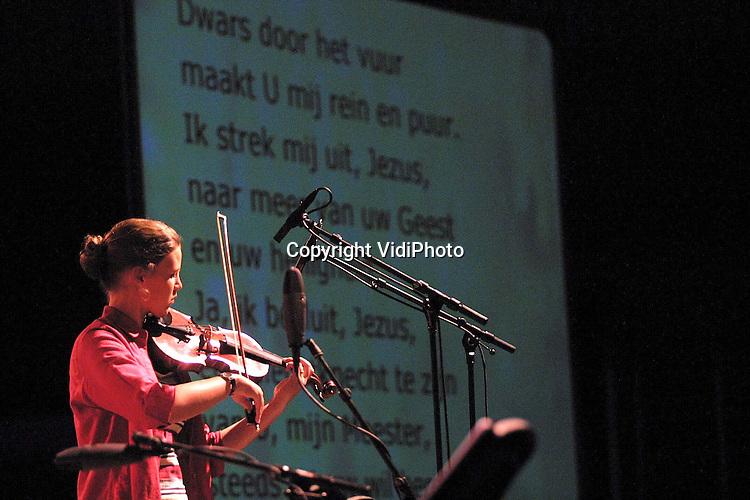 """Foto: VidiPhoto..BARNEVELD - In de Veluwehal in Barneveld zijn op Hemelvaartsdag ruim 2000 hervormde (HGJB)jongeren bijeen voor hun jaarlijkse onmoetingsdag annex muziekspektakel. De HGJB (Hervormd Gereformeerde Jeugd Bond) is de jongerenafdeling van de Gereformeerde Bond in de Nederlandse Hervormde Kerk. Thema van de dag was """"Vurig Verlangen"""". Hoogtepunt was het optreden van de gospelgroep Les Anges, geformeerd uit Afrikaanse asielzoekers die op dit moment in Nederland verblijven. Foto: Een gospelgroep van de HGJB-jongeren zelf."""