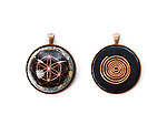 Orgonite pendant spiritual healing stone with the flower of life design on the front and copper wire spiral on the back isolated on white background
