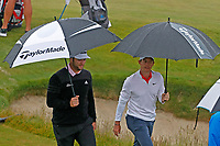 From left to right Jon Rahm (ESP) and Rory McIlroy (NIR) walk to the 12th tee in the rain under an umbrella during the Wednesday practice round of the 118th U.S. Open Championship at Shinnecock Hills Golf Club in Southampton, NY, USA. 13th June 2018.<br /> Picture: Golffile | Brian Spurlock<br /> <br /> <br /> All photo usage must carry mandatory copyright credit (&copy; Golffile | Brian Spurlock)