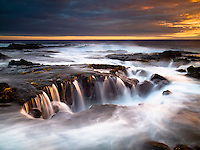Waves rush around and through a hole along the rocky shoreline of Keahole Point, Big Island.