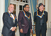 Pianist, singer, and songwriter Billy Joel, left, pianist, keyboardist, bandleader and composer Herbie Hancock, center, and musician and songwriter Carlos Santana wait to pose for a group photo with the other two recipients of the 2013 Kennedy Center Honors following a dinner hosted by United States Secretary of State John F. Kerry at the U.S. Department of State in Washington, D.C. on Saturday, December 1, 2013.  The 2013 honorees are opera singer Martina Arroyo; pianist, keyboardist, bandleader and composer Herbie Hancock; pianist, singer and songwriter Billy Joel; actress Shirley MacLaine; and musician and songwriter Carlos Santana.<br /> Credit: Ron Sachs / CNP