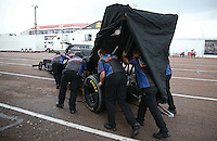 Apr. 27, 2013; Baytown, TX, USA: Crew members push the car of NHRA top fuel dragster driver David Grubnic back to the pits during a rain delay to qualifying for the Spring Nationals at Royal Purple Raceway. Mandatory Credit: Mark J. Rebilas-