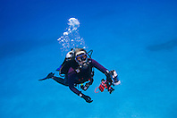 Woman scuba diver with underwater digital camera, West End, Grand Bahamas, Atlantic Ocean