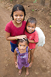 Three Nicaraguan children pose on a dirt road after swimming in Lake Nicaragua, Nicaragua