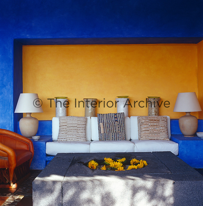 The recess behind the built-in sofa of the loggia is painted a deep yellow contrasting with the bright blue of the other walls