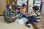 Ahlam Mazatha supervises the homework of her sons Mohammed, 13, and Abed Rahaman, 10, in their small apartment in Madaba, a sprawling Palestinian refugee camp in Jordan that has grown in recent years with the arrival of refugees--like this family--from war-torn Syria. She and her husband and three children fled Daraa in 2013 when bombing destroyed their home. Mazatha was a teacher in Syria, and her husband owned a taxi, but in Jordan they are not allowed to work by the government. The  Department of Service for Palestinian Refugees of the Middle East Council of Churches, a member of the ACT Alliance, provides a variety of services here, including medical care.