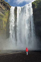 Visitor in red jacket standing in front of Skogafoss Waterfall, Iceland