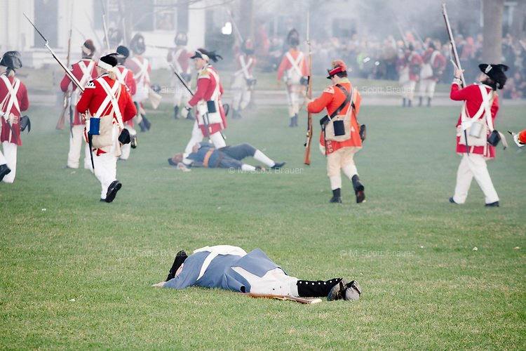 Reenactors dressed as American colonists lay on the field pretending to be injured or dead after British soldiers fired on them in a reenactment of the Battle of Lexington on Lexington Green in Lexington, Mass., on Patriots' Day, Mon., April 17, 2017.