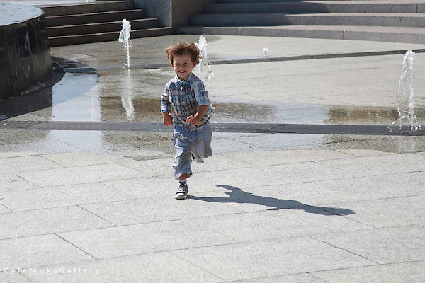 Young boy joyfully running through the fountain designed like a steel pan, Port of Spain