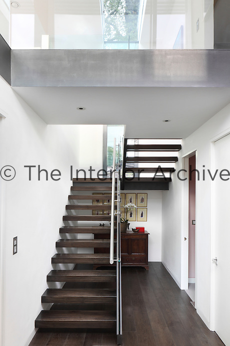 A modern open staircase with dark wood treads in a white hallway.