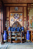 The opulent 19th century apartment  exudes sensuality, fantasy and passion. The wood walls in the dining room are the perfect backdrop for the collections of blue 18th century antique Chinese vases and Japanese Imari plates (Meiji period)