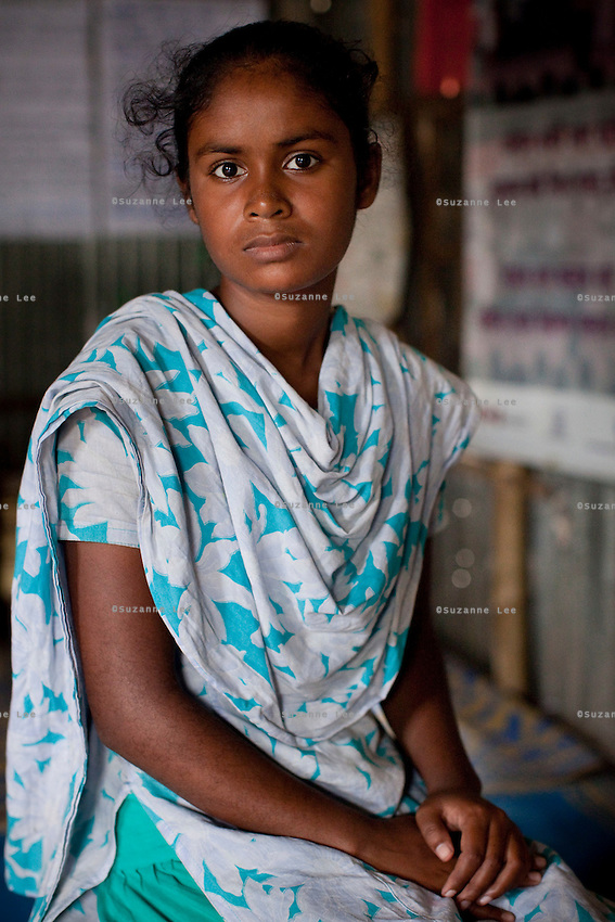 """Mony Mala (16) sits for a portrait in the meeting hut of a Children's Group in Bhashantek Basti (Slum) in Zon H, Dhaka, Bangladesh on 23rd September 2011. Mony says, """"I'm still a child, not prepared to be a wife. I feel pained that my parents don't see a point in educating me just because I'm a girl. I feel terrible when we are not able to stop a child marriage because the elders do not listen to us."""" The Bhashantek Basti Childrens Group is run by children for children with the facilitation of PLAN Bangladesh and other partner NGOs. Slum children from ages 8 to 17 run the group within their own communities to protect vulnerable children from child related issues such as child marriage. Photo by Suzanne Lee for The Guardian"""