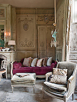 A traditional sitting room with painted walls and, unusually, a concrete floor. A sofa with a maroon red cushion stands in one corner.