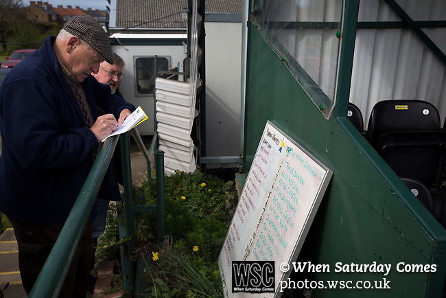 A man noting the team line-ups at Mount Pleasant before Marske United take on Billingham Synthonia in a Northern League division one fixture. Formed in 1956 in Marske-by-the-Sea, the home club had secured automatic promotion to the Northern Premier League two days before and were in the midst of a run of six home games in 10 days as they attempted to overtake Morpeth Town to win the league. They won this match 6-1 against already relegated Billingham, watched by a crowd of 196.