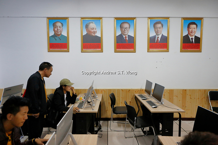 Nangqen County, Yushu Tibetan Autonomous Prefecture, Qinghai Province, China - Tibetans learn underneath portraits of China's Communist leaders, August 2019.